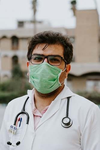 clothing man in white scrub suit wearing green mask lab coat