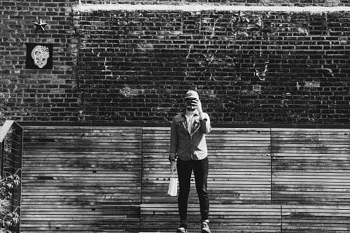 black-and-white person standing beside wall brick