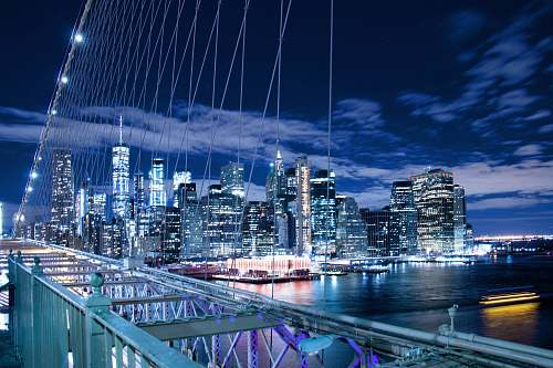 city panoramic photo of buildings through bridge cables town
