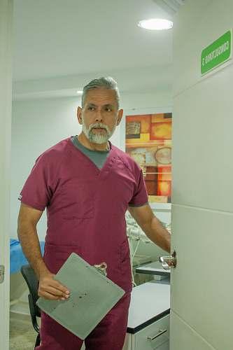 person man in blue crew neck t-shirt standing near white wooden cabinet shelf