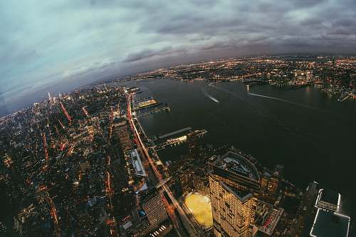 outdoors aerial photography of buildings beside calm water at night landscape