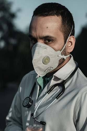 human person wearing white and gray gas mask doctor