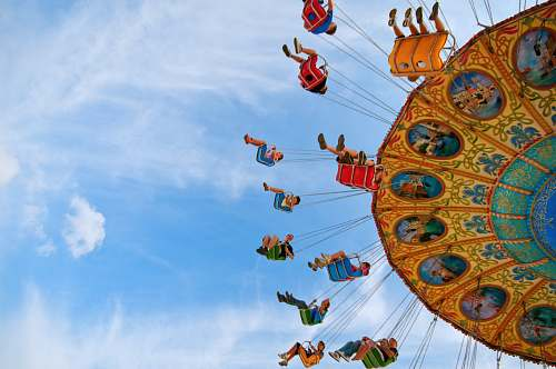people people riding carnival ride under blue skies wallpaper