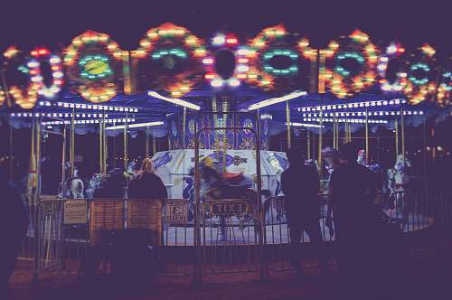 person people standing besides Merry-Go-Round during nighttime human