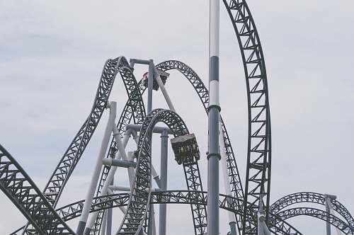 grey roller coaster under white clouds and blue sky roller coaster