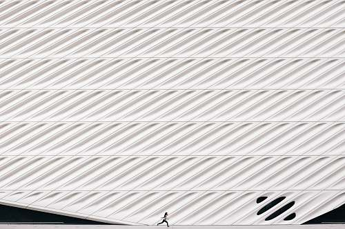black-and-white person running near white painted wall texture