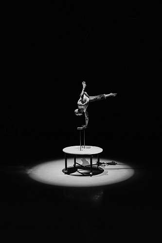 human grayscale photography of man doing stunts on round table person