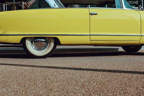 automobile photo of yellow coupe on road transportation