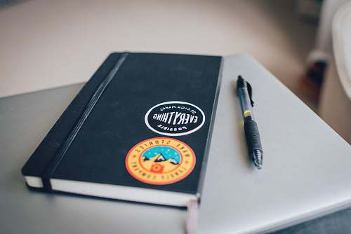 possible black book cover near black click pen notebook