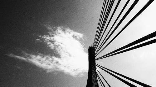 black-and-white low angle photography of bridge wire under clouds bridge