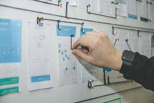 hand person working on blue and white paper on board ux