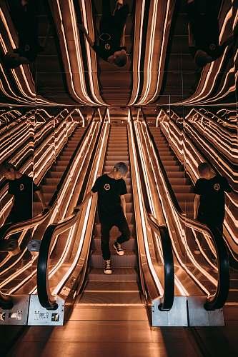 escalator man standing on escalator with string lights menswear