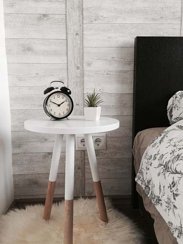 interior black alarm clock at 10:10 on white wooden table near table alarm clock