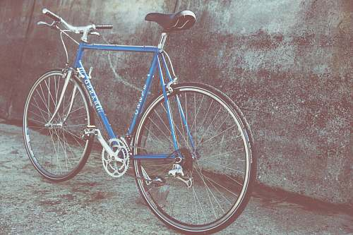 bicycle blue and gray rigid bicycle parked beside wall bike