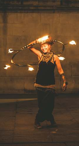 person girl wearing black and gold kameez holding hoop with fire juggling