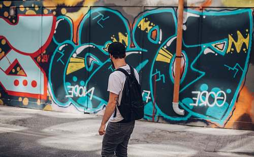 photo graffiti man wearing black backpack people free for commercial use images
