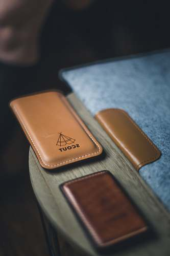 brown Leather laptop cover, wallet, and phone holder with a label that reads