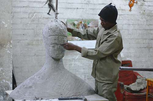 art A sculptor works in his studio sculpting a large white body and head human