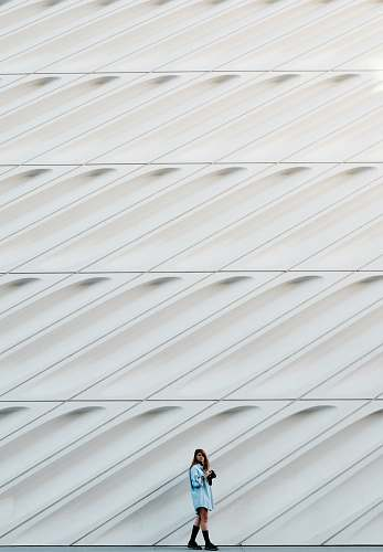 pattern woman standing beside white concrete wall wall
