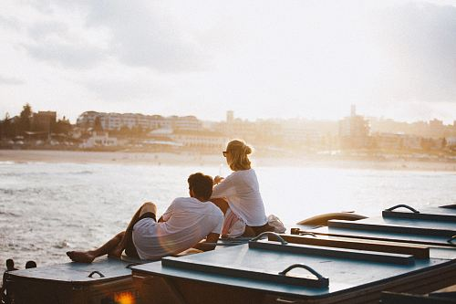 photo couple sitting on boat in front of body of water free for commercial use images