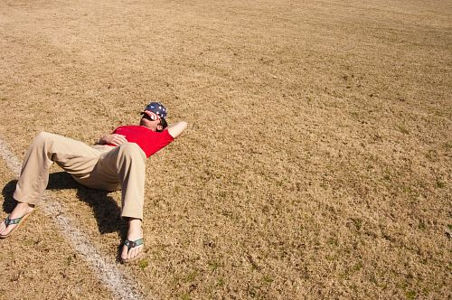 photo man in red top lying on lawn field during daytime free for commercial use images