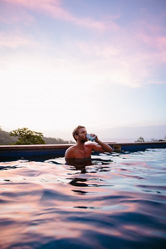 photo topless man drinking beverage while on swimming pool free for commercial use images