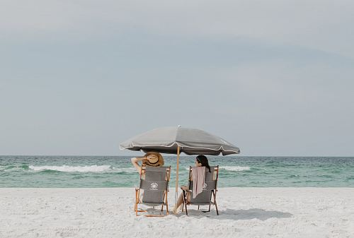 two people under beach umbrella near shoreline