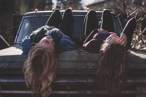 photo two women lying down on vehicle free for commercial use images