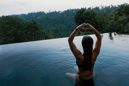free for commercial use woman in infinity pool making heart hand gesture facing green leafed trees images