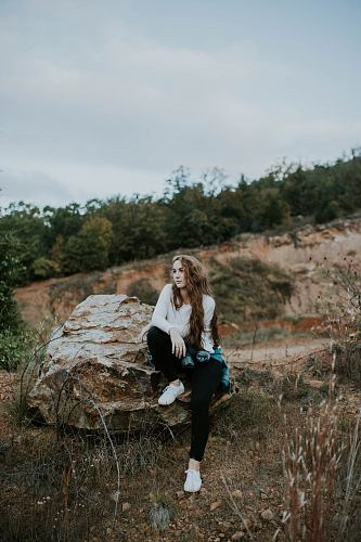 photo woman sitting on stone boulder outdoor free for commercial use images