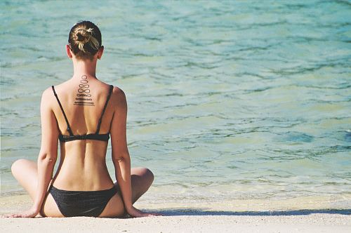 woman wearing bikini in yoga position facing sea