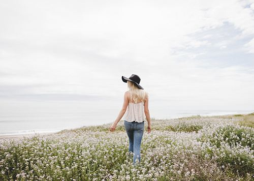 photo woman wearing black hat walking across the flower field during day time free for commercial use images