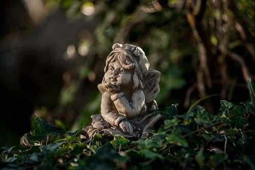 lion girl leaning forward figurine on green leaves mammal