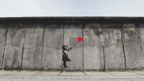 berlin girl playing heart balloon wall artwork germany