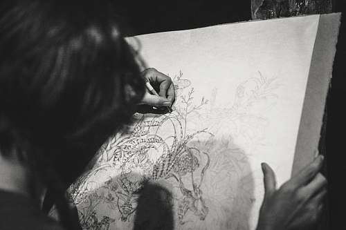 grey grayscale photo of a woman drawing a flowers black-and-white
