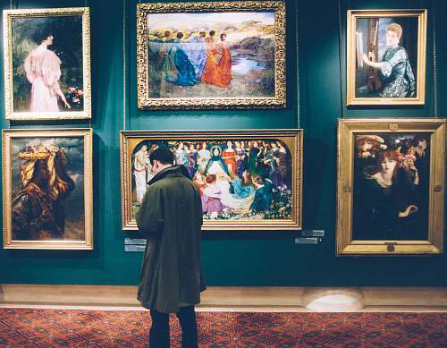 painting person standing near six paintings inside gallery person