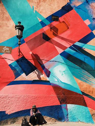 photo human man sitting on wall with artwork and lamp morocco free for commercial use images
