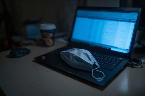 electronics black laptop computer beside black framed eyeglasses on brown wooden table computer