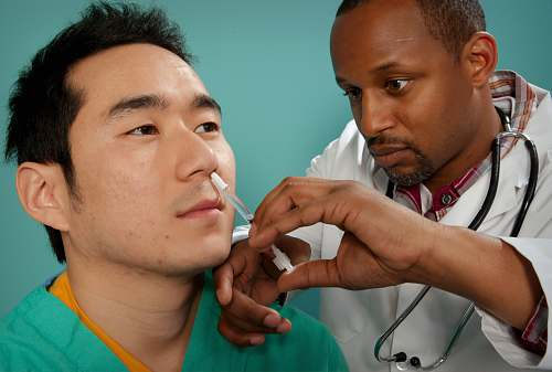human doctor suctioning on man's nose patient