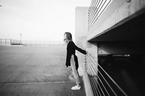 photo grayscale photography of woman standing near building free for commercial use images