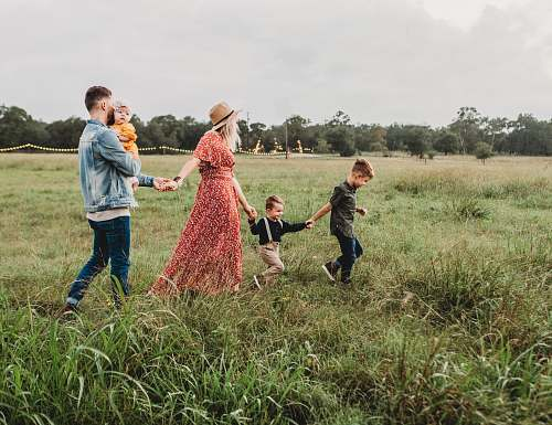 family woman holding man and toddler hands during daytime field