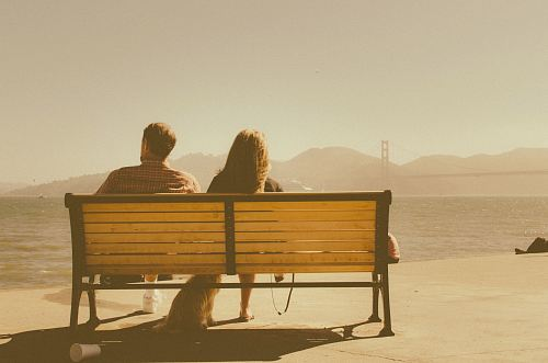 photo man and woman sitting on bench beside body of water free for commercial use images