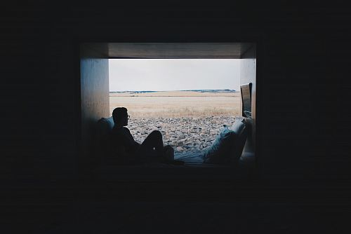 photo person sitting while looking outside free for commercial use images
