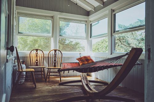 photo photography of grey, white, and brown wooden house interior with three brown wooden Windsor chairs beside brown hammock with glass windows free for commercial use images