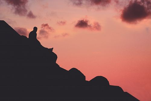 photo silhouette of man sitting on cliff free for commercial use images