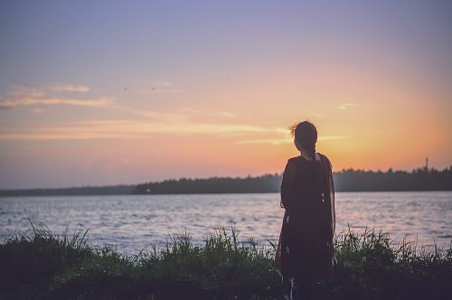 photo silhouette photography of woman looking at body of water free for commercial use images