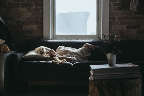photo woman lying on sofa near closed window during daytime free for commercial use images