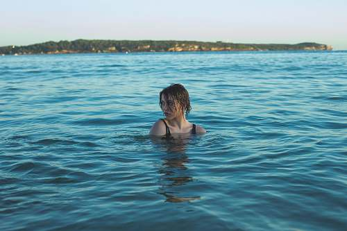 swimming photography of woman in black swimming wear soaked in sea people