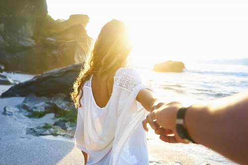 woman person holding woman's hand beside sea while facing sunlight couple