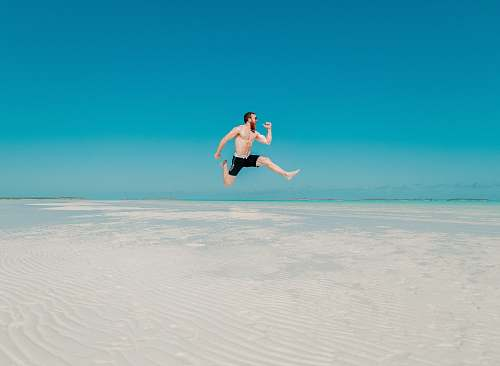 human time lapse photography of man jumping at seashore person